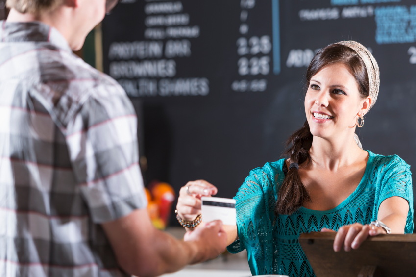 Woman working in restaurant taking payment from customer
