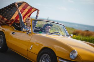 Young women with American flag driving a yellow convertible
