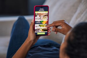 Woman lying on couch using food delivery app on smartphone. Close up of african woman hands holding cellphone and ordering food online. Girl using smart phone to get home delivered take away lunch.